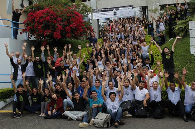 Decenas de personas levantan las manos con alegría, mientras posan para la foto oficial de Drupal Camp en 2015