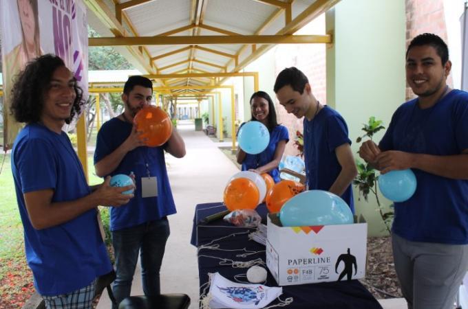 Personas organizadoras de Drupal Camp sonríen mientras inflan globos del evento
