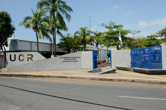Frente de un edificio que dice Universidad de Costa Rica Sede del Pacífico, pared de concreto con portones de color azul.
