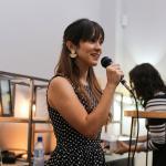 mujer de 26 años con vestido negro con puntitos blancos, sujeta un micrófono, parece que está exponiendo a una audiencia y su rostro se ve feliz
