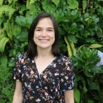 Katherine está de pie, lleva puesto un vestido con estampado floral y está sonriedo en un lugar con mucha vegetación.